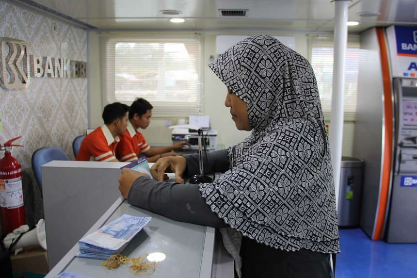 Madam Ningsih gets her banking done on the boat, saving her the bother of travelling from Untung Jawa to mainland Java.