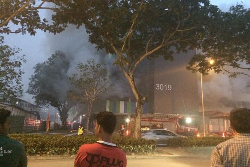 Smoke continues to billow out from Block 3019 Ubi Road 1 as SCDF officers control traffic, on Sept 14, 2015.