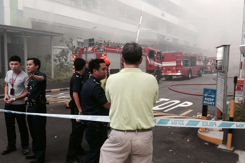 SCDF officers preventing passers-by from getting too close to the fire as smoke billows out from Block 3019 Ubi Road 1 on Sept 14, 2015.