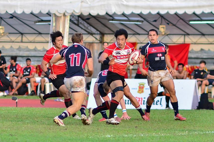 Japan (in red and black) scored a flurry of tries inside the final 10 minutes to defeat Hong Kong 24-19 in the championship match of the HSBC Asian Rugby Sevens series held at the Yio Chu Kang Stadium on Nov 10, 2013.