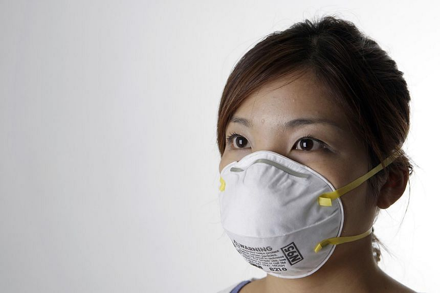 A woman wearing a N95 mask.