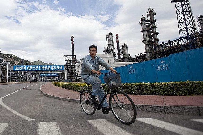 China's SOEs had combined assets of over 100 trillion yuan as of July last year. (Right) A worker cycling through a Sinopec refinery in Beijing. The firm is China's largest SOE, with an income of 2.83 trillion yuan last year. An ICBC employee working