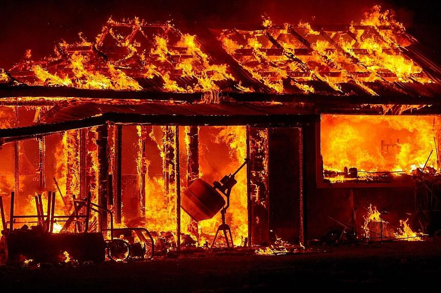 A house in flames amid the Valley Fire in Siegler Springs. The Valley Fire and Butte Fire have charred large swathes of land.