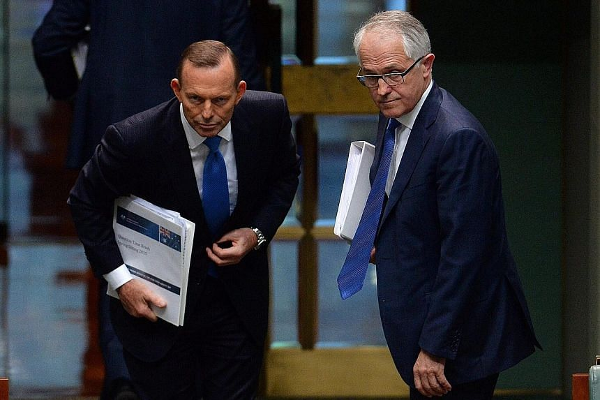 Mr Tony Abbott (left) and Mr Malcolm Turnbull at Parliament House in Canberra yesterday. Mr Turnbull has indicated that his top priority will be to focus on the economy and innovation.