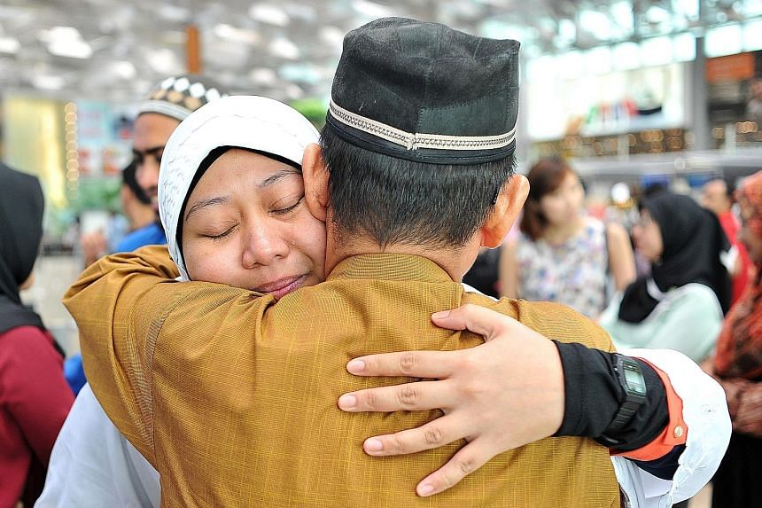 Nurse Nur Asyiqin Jumari (left), 30, hugging her father, retired bus driver Jumari Suri, 65, at Changi Airport yesterday. She was among the latest batch of Muslim Singaporeans pilgrims heading to Mecca for their haj. Dr Yaacob Ibrahim was there to se