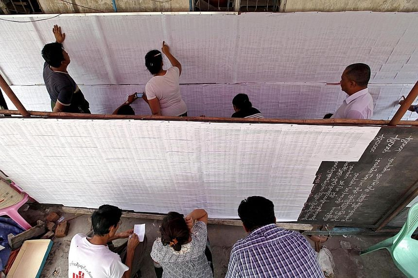 People checking their names on a voters' list in Kamayut town in Yangon, Myanmar, yesterday. The three main power blocs - the ruling military-backed Union Solidarity and Development Party, the opposition National League for Democracy (NLD) and ethnic