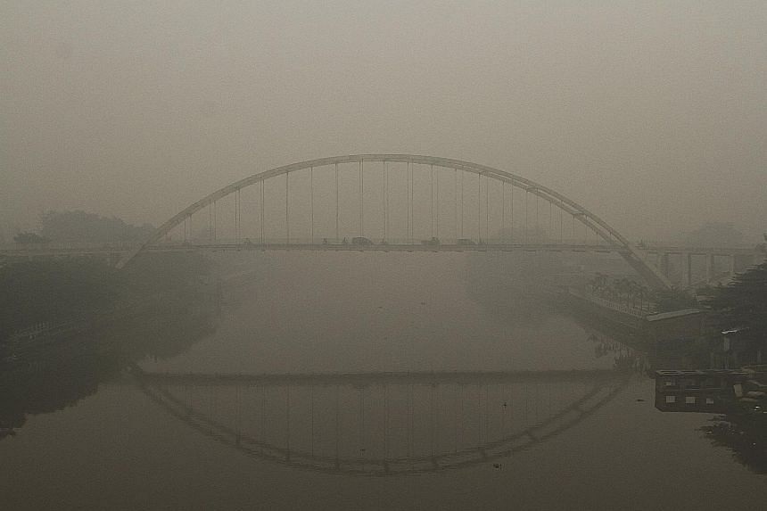 A haze-shrouded bridge over the Siak River in Pekanbaru, Riau province, yesterday. The deteriorating situation has prompted Indonesian President Joko Widodo to instruct the police and armed forces chiefs to deploy additional personnel to help combat
