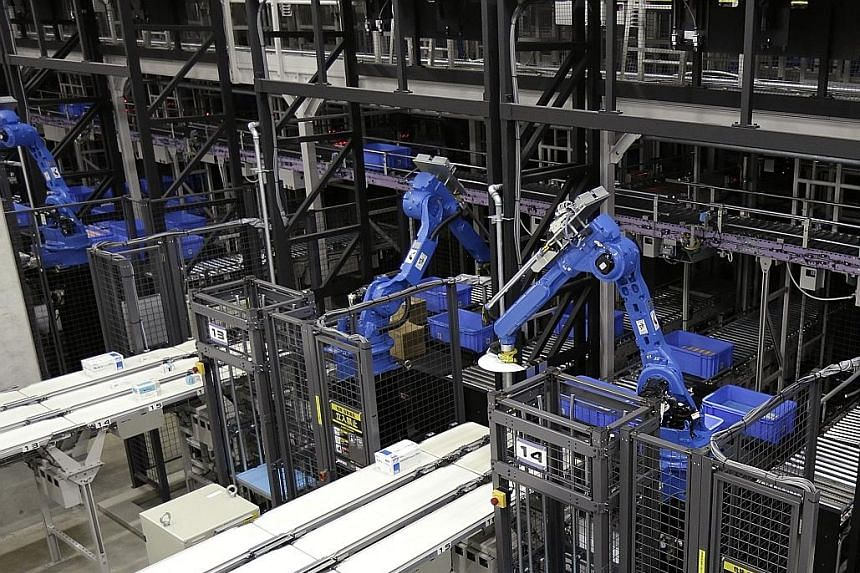 Robots pick items to place on conveyors for sorting at a centre operated by Toho. By 2025, robots could shave off 25 per cent of factory labour costs in Japan, according to Boston Consulting Group.