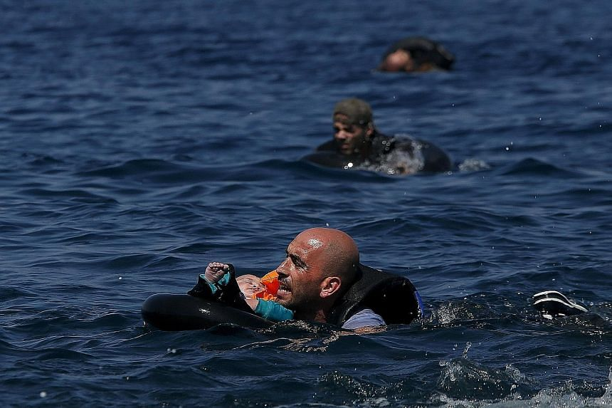 Migrants swimming to shore in lifetubes after their dinghy deflated some 100m from the Greek island of Lesbos on Sunday. European interior ministers yesterday held crisis talks, with Germany, France and the bloc's executive commission trying to overc