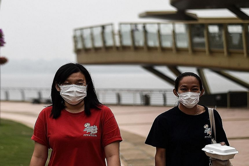 Women wearing masks because of the haze in Putrajaya, Malaysia, on Sunday. The haze problem persists because its systemic causes are not being addressed.