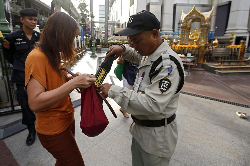 A security guard checks a worshipper's bag at the Erawan Shrine (background) in Bangkok, Thailand, on Sept 9, 2015.