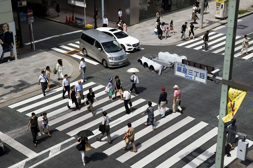 People cross a street in the Ginza shopping district of Tokyo, Japan.