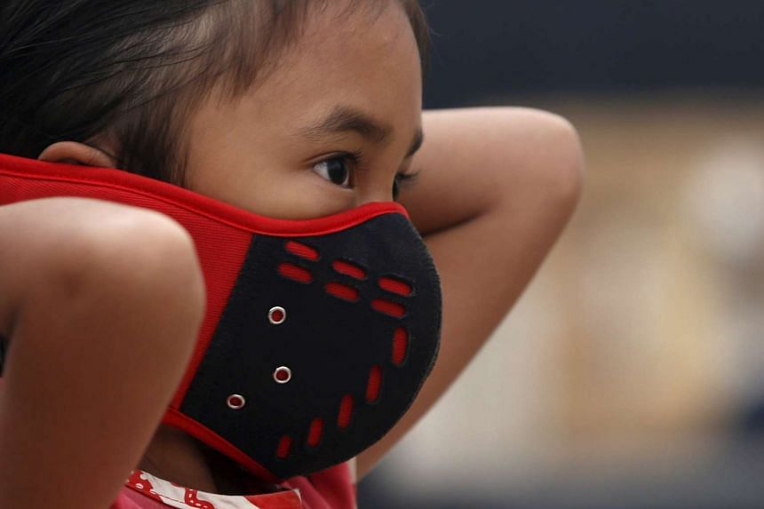 A girl uses her mask as she helps her father sell rice at a stall at Rambutan village in Banyuasin, Indonesia.