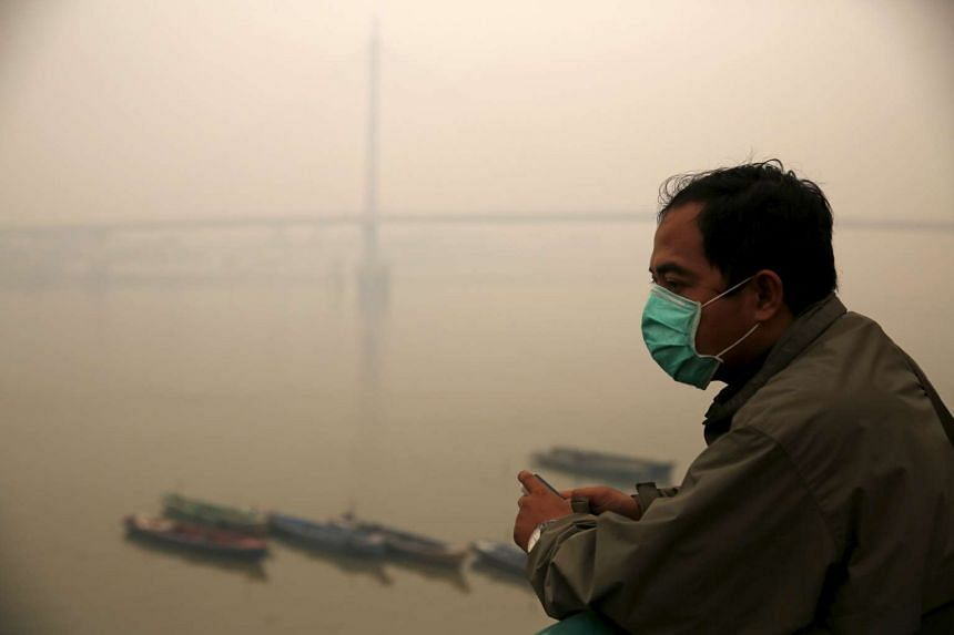 A worker stands as the haze shrouded Batanghari River in Jambi, on Indonesia's Sumatra island, on Sept 15, 2015.