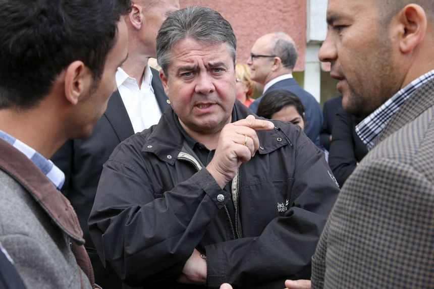 German Vice Chancellor Sigmar Gabriel talking with refugees in Wolgast, northeastern Germany on Sept 14, 2015