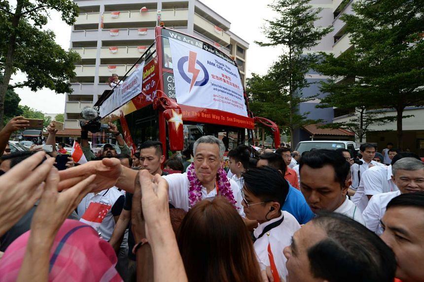 Prime Minister Lee Hsien Loong shaking hands with residents from Ang Mo Kio GRC during a victory parade with his team on Sept 12, 2015.
