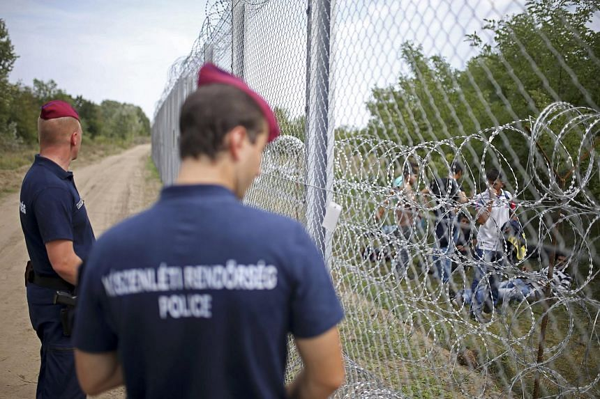 Policemen watch as migrants walk on the other side of the border from Serbia near Asttohatolom, Hungary, on Sept 15, 2015.
