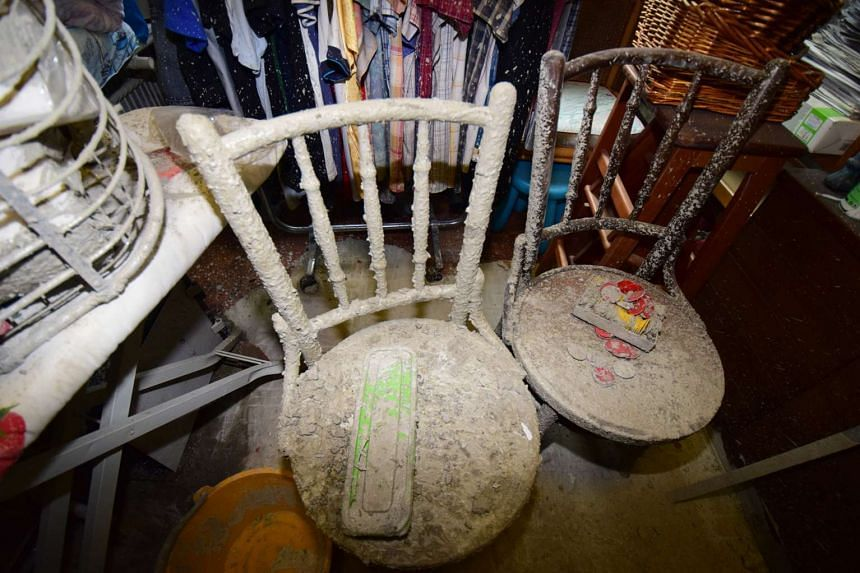 Dust covered chairs in the storeroom, where part of the ceiling was damaged.