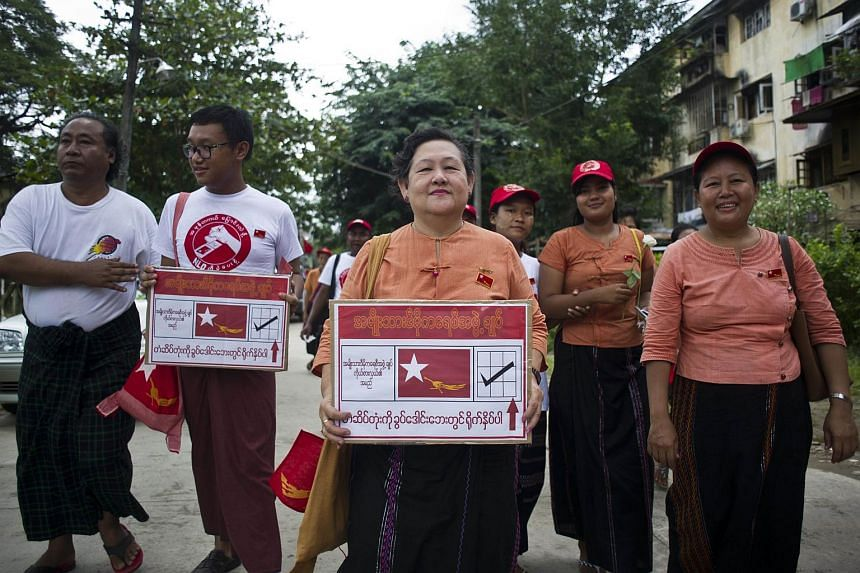 Members of the National League for Democracy (NLD) party walk down a road as they campaign for the upcoming Nov 8 general election, in Yangon on Sept 15, 2015.