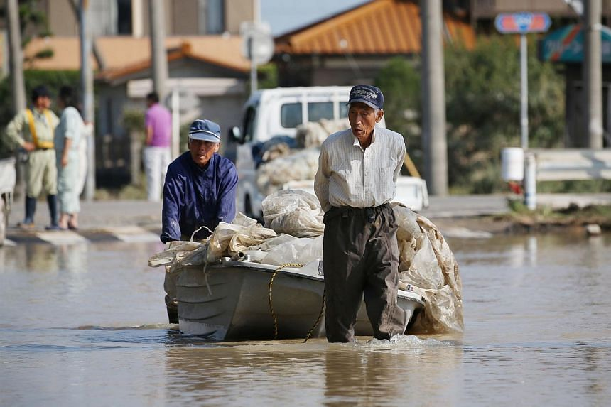 Local residents Noshimasa Yoshida (right) and Ei Hirose carry their agriculture materials with a boat at Joso in Ibaraki prefecture on Sept 15, 2015.