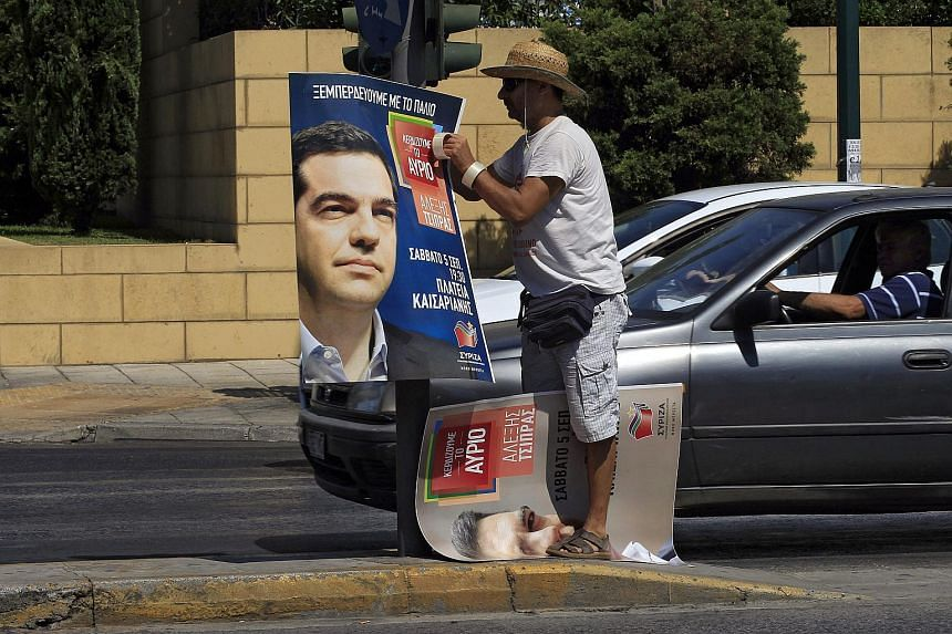 A man hangs a poster of former Prime Minister and President of Syriza party Alexis Tsipras, on a traffic light, in Athens, Greece, on Sept 4, 2015.