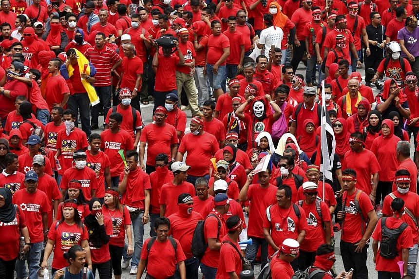 """""""Red Shirt"""" demonstrators gather for a rally to celebrate Malaysia Day and to counter a massive protest that called for Prime Minister Najib Razak's resignation over a graft scandal."""