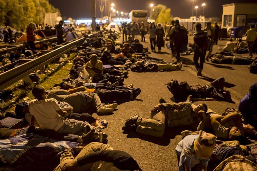 Migrants sleeping on a highway in front of a barrier at the border with Hungary near the village of Horgos, Serbia, on Sept 15, 2015.