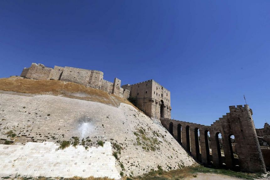 """Aleppo's historical citadel with its wall damaged by the impact of a rocket fired during fighting between government forces and rebels. Archeological sites in Syria are being looted """"on an industrial scale,"""" with proceeds being used to fund Islamic"""