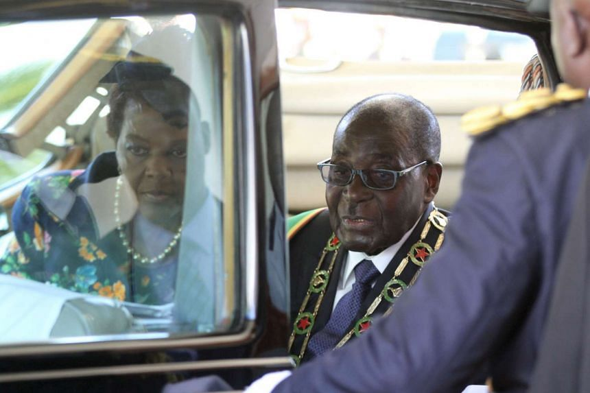 Mugabe (right) and his wife Grace leave the State House to officially open Zimbabwe's parliament.