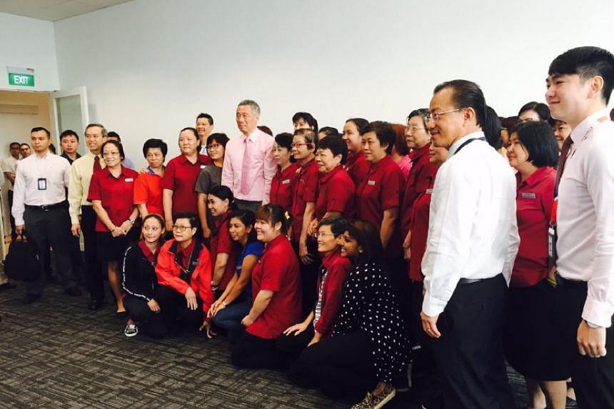 PM Lee (centre) meeting trainee cashiers at the training centre in FairPrice Hub.