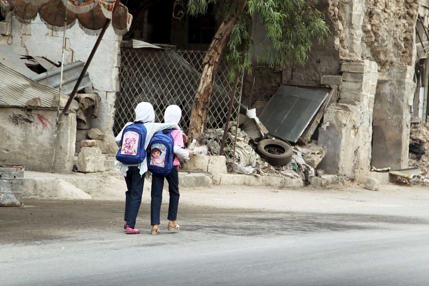 Girls walk to school in Old Aleppo, Syria on Tuesday.