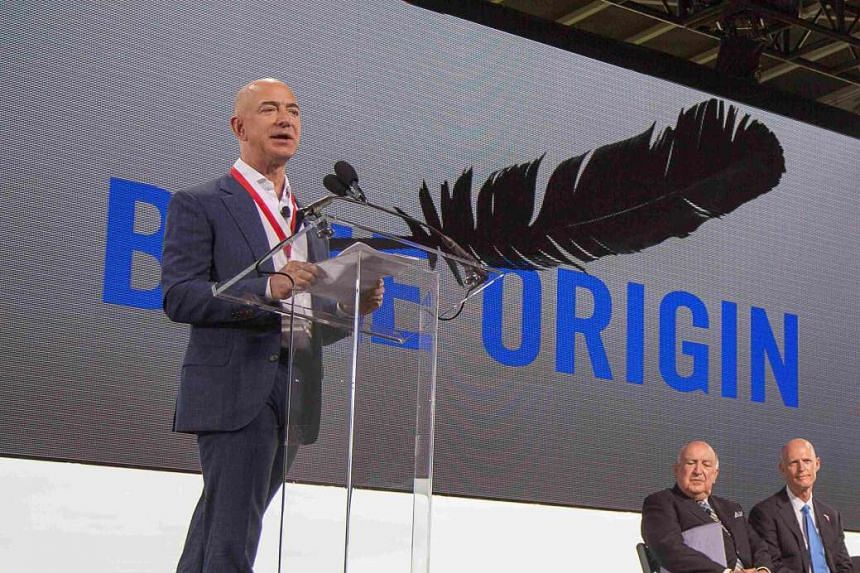 Amazon founder and Blue Origin founder Jeff Bezos (L)announces plans to build a rocket manufacturing plant and launch site at Cape Canaveral Air Force Station in Florida on Tuesday.