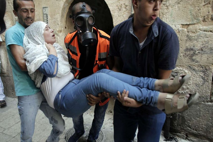 Palestinian paramedics carry a woman after Israeli security forces fired tear gas and pepper spray in a street of the Muslim quarter in Jerusalem's Old City during scuffles with Israeli riot police on Tuesday.