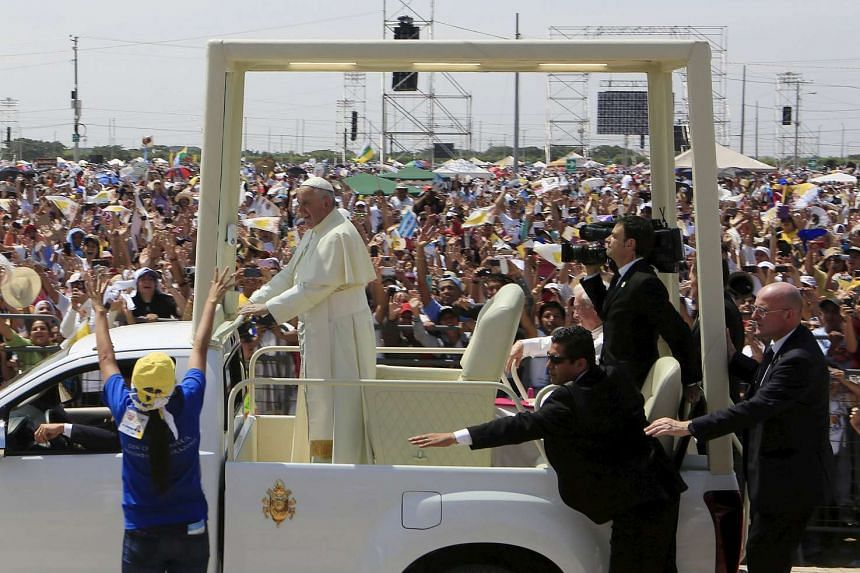 Pope Francis drives past the faithful as security reaches out to stop a woman trying to approach the Popemobile during a visit to Ecuador in July.