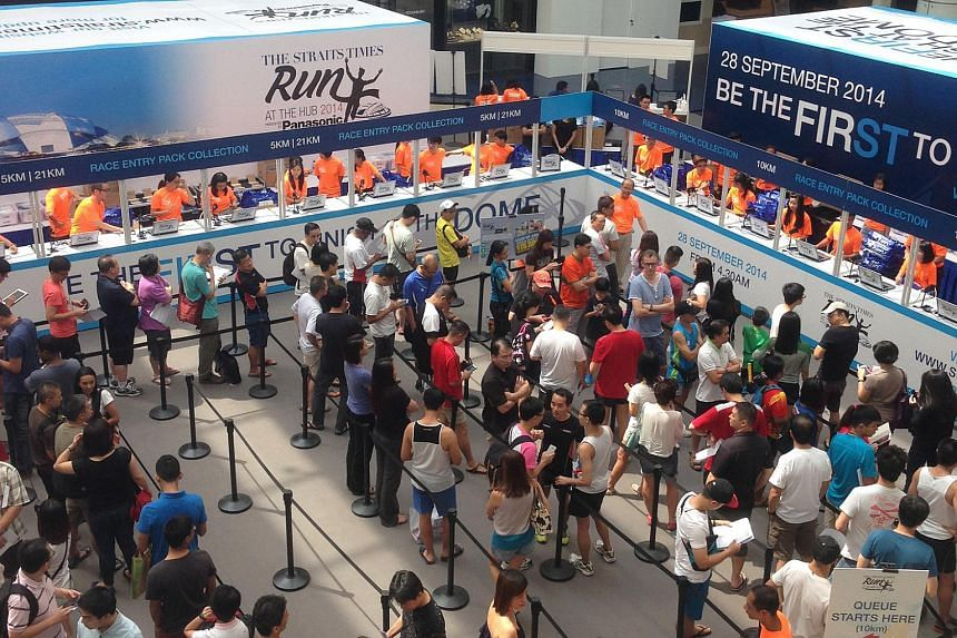 Participants queuing up to collect their race packs for the Straits Times (ST) Run at the Hub on Sept 7, 2014.