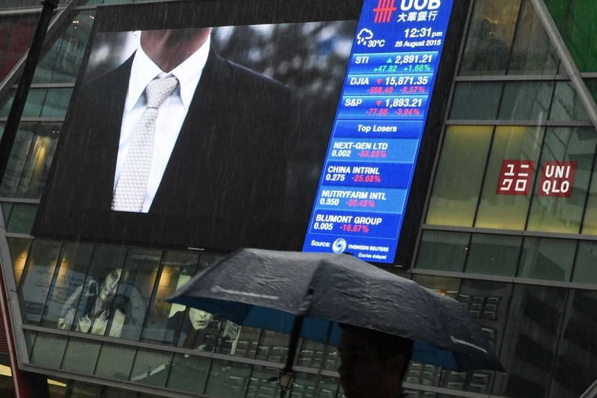 A file picture of a digital screen displaying stocks index data in Singapore. PHOTO: AFP
