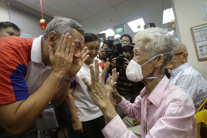 Prime Minister Lee Hsien Loong beckons an elderly resident to adjust her AIR+ Smart Mask after putting it on for her.