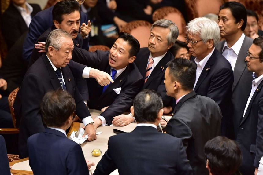 Opposition lawmakers surround chairman Yoshitada Konoike (left) as lawmaker Masahisa Sato (second left) gestures during the Upper House's ad hoc committee meeting on the controversial security bills, at the National Diet in Tokyo on Sept 17, 2015.