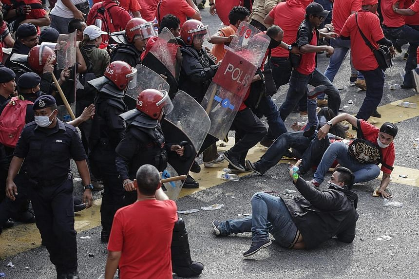 Demonstrators (left) waving flags and chanting slogans at the rally in Kuala Lumpur yesterday. Although riot police were present to ensure the situation did not get out of hand, some clashes broke out (below).