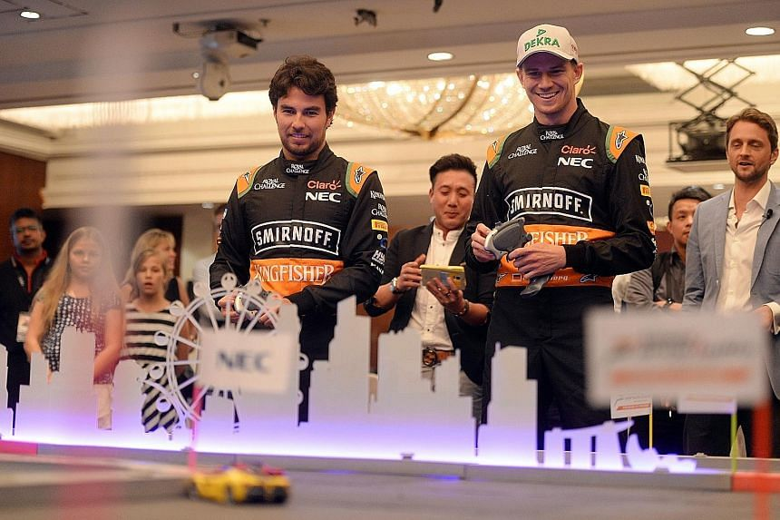 Force India drivers Sergio Perez (left) and Nico Huelkenberg racing toy cars around a mini-circuit during an NEC promotional event at the Marina Mandarin hotel yesterday.