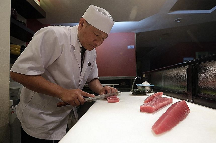 Chef Kevin Yong preparing bluefin tuna in Hinoki Japanese Dining. The fish won't be on the menu for three weeks next month.