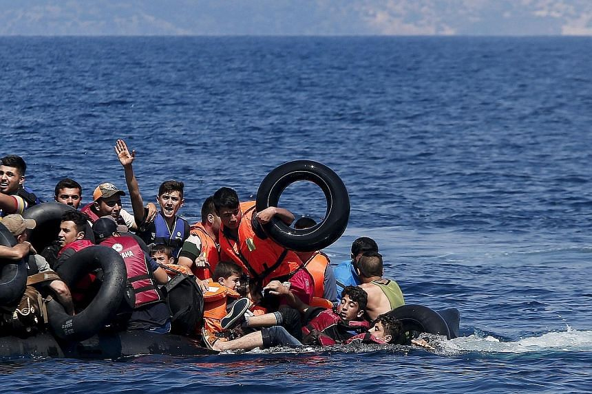 Above: Refugees falling into the sea after their dinghy deflated before reaching the Greek island of Lesbos on Sunday. Left: Refugees entering a registration camp after they crossed the border between Greece and Macedonia yesterday.