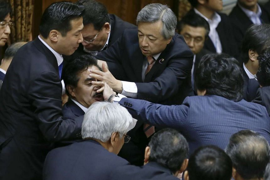Japanese opposition lawmakers try to cover the face of Masahisa Sato, deputy chairman of the upper chamber special committee on security legislation, during a meeting on Sept 17, 2015.