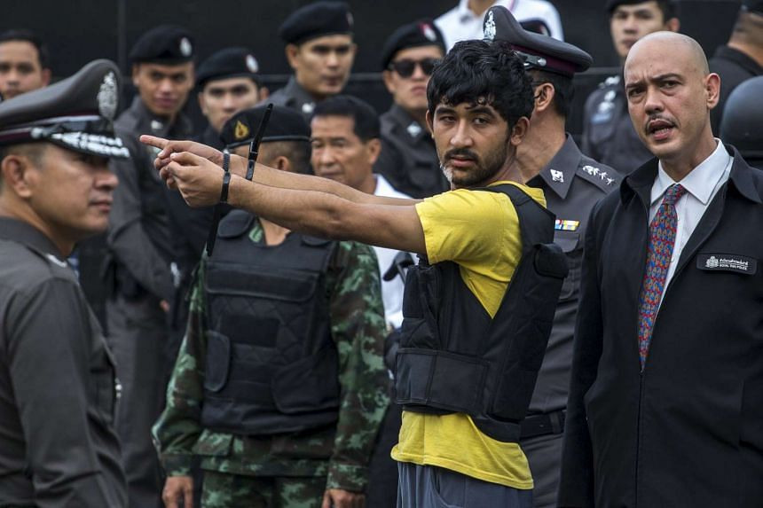 A Bangkok blast suspect pointing during a crime re-enactment near the bomb site at Erawan Shrine on Sept 9, 2015.