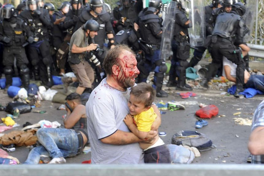 An injured migrant carries a child during clashes with Hungarian riot police at the border crossing with Serbia in Roszke, Hungary.
