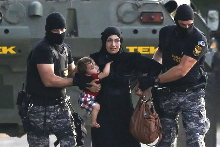 Hungarian riot policemen escort a migrant woman and her child in Roszke, Hungary on Sept 16, 2015.
