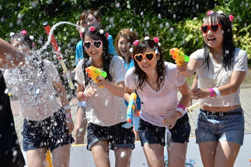 Japanese youths played with water guns in August 2015 as Tokyo temperatures climbed to over 30 deg C.
