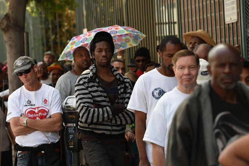 Unemployed and homeless people lining up for a free meal and new shoes in Los Angeles, California, on April 3, 2015.