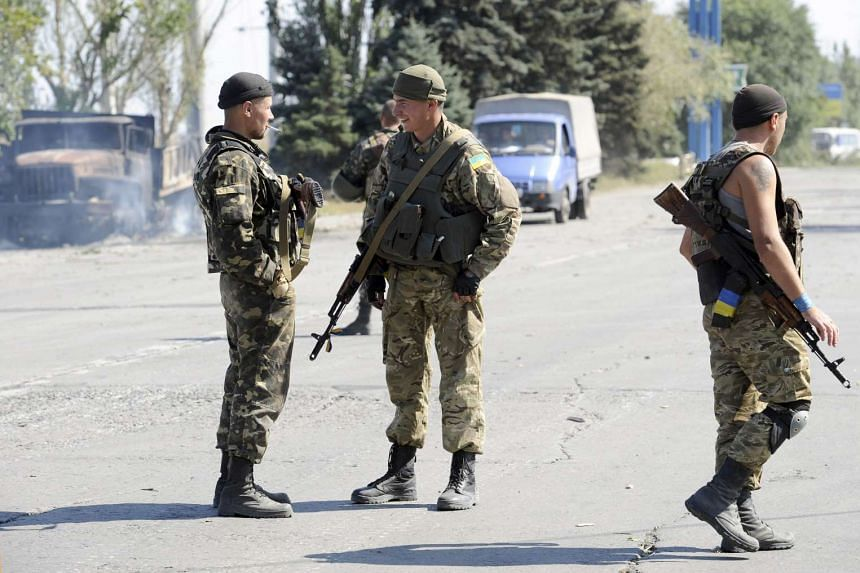 Ukrainian servicemen standing guard at an Ukrainian army checkpoint on the outskirts of the key south-eastern port city of Mariupol on Sept 7, 2015.