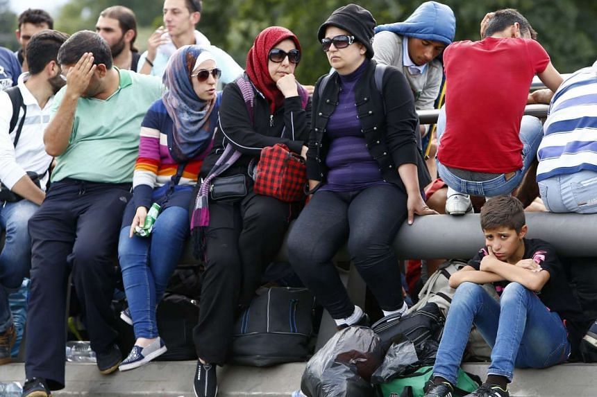 Migrants wait to cross the border from Austria to Germany near Freilassing, Germany, on Sept 17, 2015.